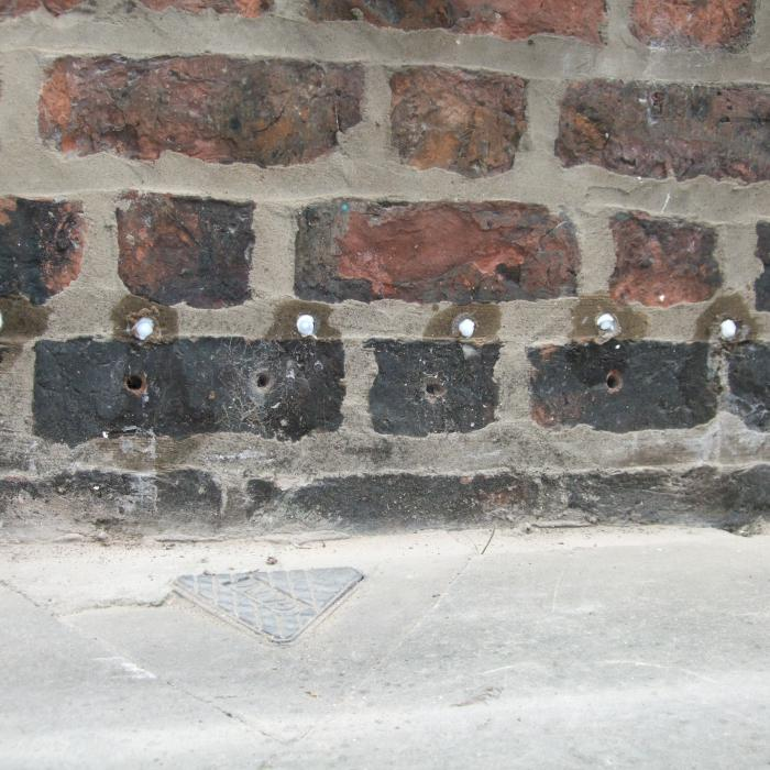 A recently installed retrofit chemical injection damp proof course by our operatives note how the silane/siloxane cream begins to diffuse through the mortar bed joint to form an effective moisture resistant barrier.