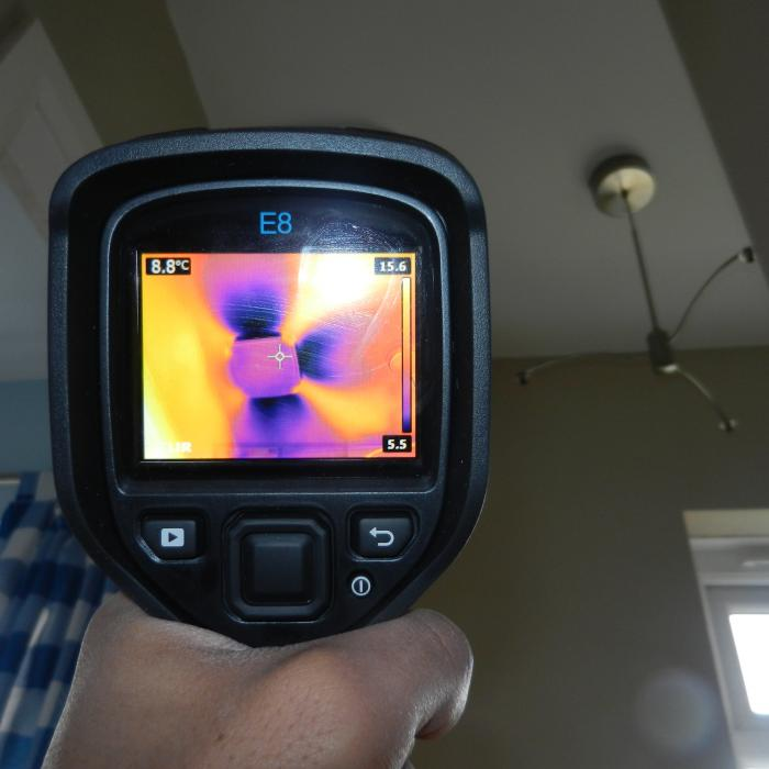 This is a thermal image taken of a Positive Input Ventilation (PIV) system installed into the first floor landing ceiling of a property which had previously been suffering with issues of condensation.  The Positive Input Ventilation system is designed to filter air from the loft space of the building into the property through a diffuser and G4 filter which distils the stale air within the property forcing it out through natural ventilation sources and creating valuable air exchanges. The results are noticeably better atmospheric conditions and a lesser risk of issues with condensation.  The images shows the cooler air from within the loft space being distributed by the diffuser on the ceiling.
