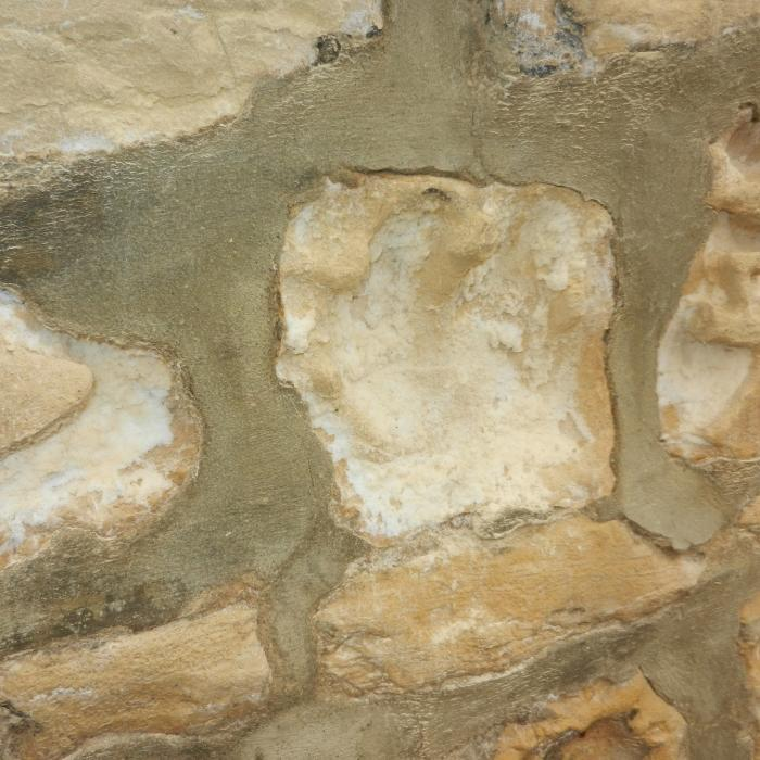 Here is an image of a soft sandstone wall which has recently been inappropriately pointed with a dense cementitious mortar unfortunately to the detriment of the stone work. The stone wall has been constructed with lime mortar which has similar properties to the stone allowing moisture to freely evaporate. During refurbishment of the property however the owner instructed a builder to re-point the wall which he has done, although with no understanding of how the wall breaths.  In this situation the original lime mortar has been raked back and the wall re-pointed with cement mortar,  which as a consequence prevents the wall from breathing evenly as it did before. The cement pointing prevents evaporation through the mortar forcing all moisture within the wall to evaporate through the face of the stonework leaving behind salt deposits and greatly accelerating the decay of the stonework, as can be seen. Re-pointing soft stone with cement mortar should strongly be avoided.